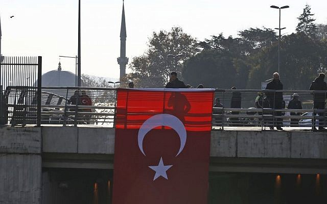 People walk on a street decorated with a Turkish flag near the Besiktas football club stadium the day after two explosions at the site killed 38, Istanbul, December 11, 2016. (AP/Emrah Gurel)