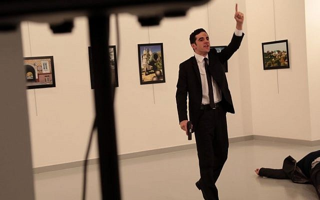 Gunman Mevlut Mert Altintas gestures near to Andrei Karlov on ground, the Russian Ambassador to Turkey at a photo gallery in Ankara, Turkey, Monday, Dec. 19, 2016. (AP Photo/Burhan Ozbilici)