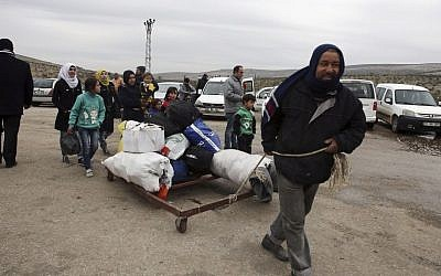 A Syrian man pulls his family's belongings after they were evacuated from Aleppo, near Idlib, Syria, Friday, Dec. 16, 2016. (AP Photo)