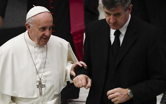 Pope Francis holds his assistant Sandro Mariotti's arm as he walks down steps during his weekly general audience, in the Pope Paul VI hall, at the Vatican, Wednesday, Dec. 7, 2016. (AP Photo/Andrew Medichini)