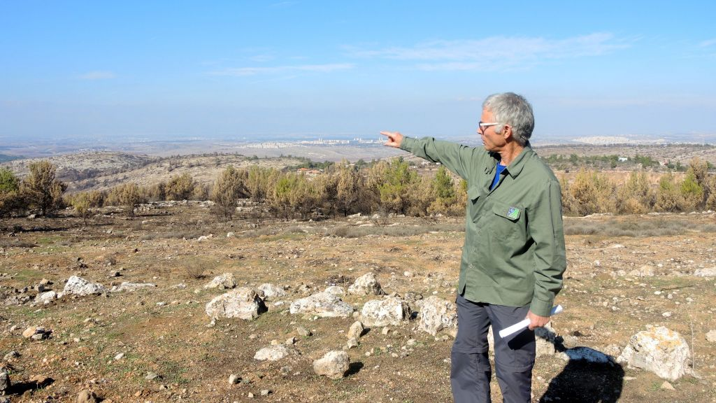 Chanoch Zoref, the forest supervisor for Jerusalem National Fund/Keren Keyemet L'Yisrael's in the Judean Hills region, points out some of the fire damage outside of Jerusalem on December 12, 2016. The fire in this area was largely a ground fire, which is less intense and does not always consume the trees. (Melanie Lidman/Times of Israel)