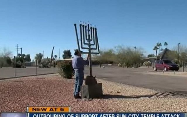 A man works to fix the menorah outside Temple Beth Shalom in Sun City, Arizona, that was damaged in suspected hate crime on December 25, 2016. (screen capture: ABC 15 Arizona)