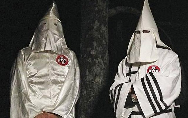 Two masked Ku Klux Klansmen stand on a muddy dirt road during an interview near Pelham, NC on Dec. 2, 2016. (AP Photo/Jay Reeves)