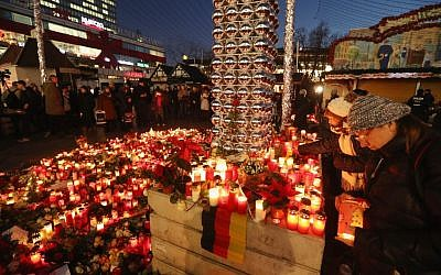 Mourners laying flowers and candles at a makeshift memorial in Berlin near the site where two days earlier, a man drove a heavy truck into a Christmas market in an apparent terrorist attack, Dec. 21, 2016. (Sean Gallup/Getty Images via JTA)