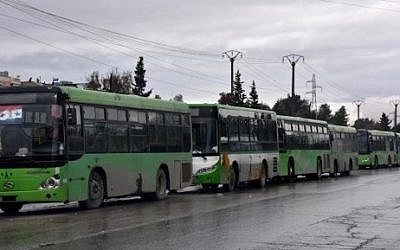 Buses wait to evacuate civilians from eastern Aleppo, December 14, 2016. / AFP PHOTO / George OURFALIAN