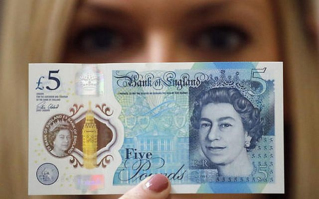 A Bank of England employee shows the new five pound note at the Bank of England Museum in London on Sept. 6, 2016.  (AP Photo/Frank Augstein, File)