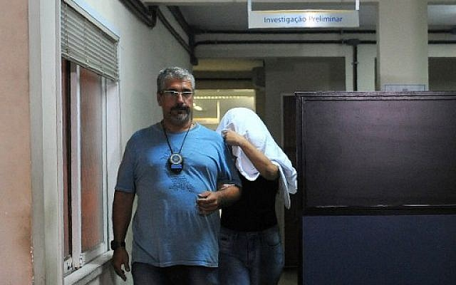 A Brazilian civil policeman escorts the wife of Greece's ambassador to Brazil Kyriakos Amiridis, Francoise de Souza Oliveira, who murdered him in a plot hatched with her police officer lover, who confessed to the crime, on December 30, 2016 in Rio de Janeiro. (AFP/Fabio Teixeira)