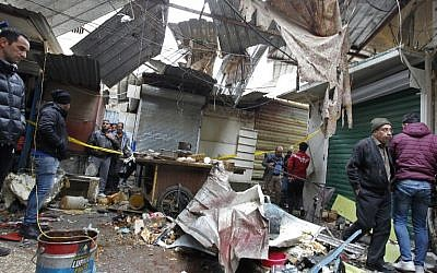 Iraqis look at the aftermath following a double bomb attack in a busy market area in Baghdad's central al-Sinek neighbourhood, December 31, 2016. (AFP/SABAH ARAR)