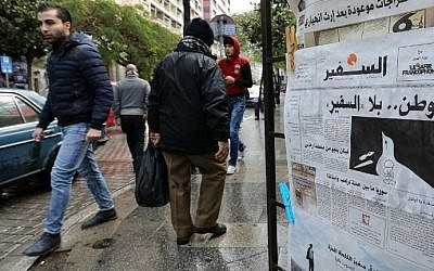 People walk past a newspaper stand displaying the As-Safir newspaper in Beirut's Hamra neighborhood on December 31, 2016. (Anwar Amro/AFP)