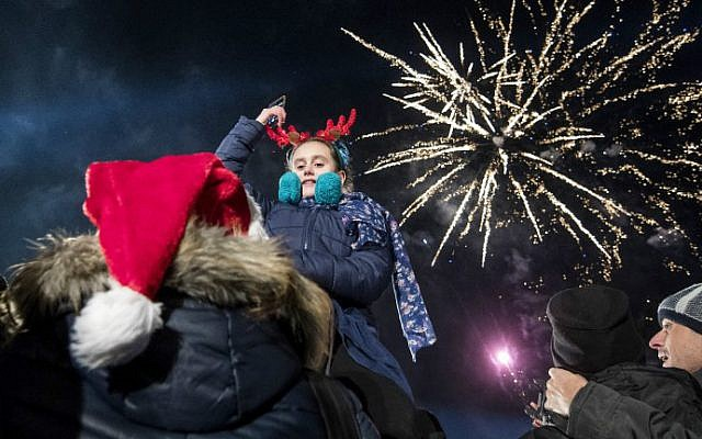 Revellers watch a fireworks display as they celebrate the New Year's countdown in Sofia, Bulgaria on January 1, 2017. (Nikolay Doychinov/AFP)