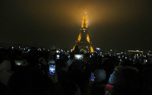 Revellers gather at the foot of the Eiffel Tower for the New Year's celebration on January 1, 2017 in Paris. (Martin Bertrand/AFP)