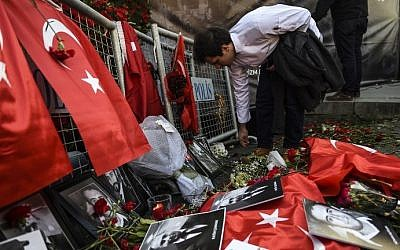 A man lays flowers in front of the Reina nightclub on January 3, 2017, in Istanbul, after a gunman killed 39 people on New Year's night.  AFP/BULENT KILIC)