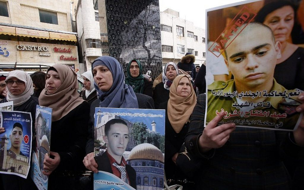 Rajaa (C), holds a poster of her son Abdul Fatah al-Sharif as Palestinians gather in the street in the West Bank town of Hebron on January 4, 2017, during the trial of Israeli soldier Elor Azaria (portrait-C) who killed Sharif, a wounded Palestinian stabber as he lay on the ground, (AFP PHOTO / HAZEM BADER)