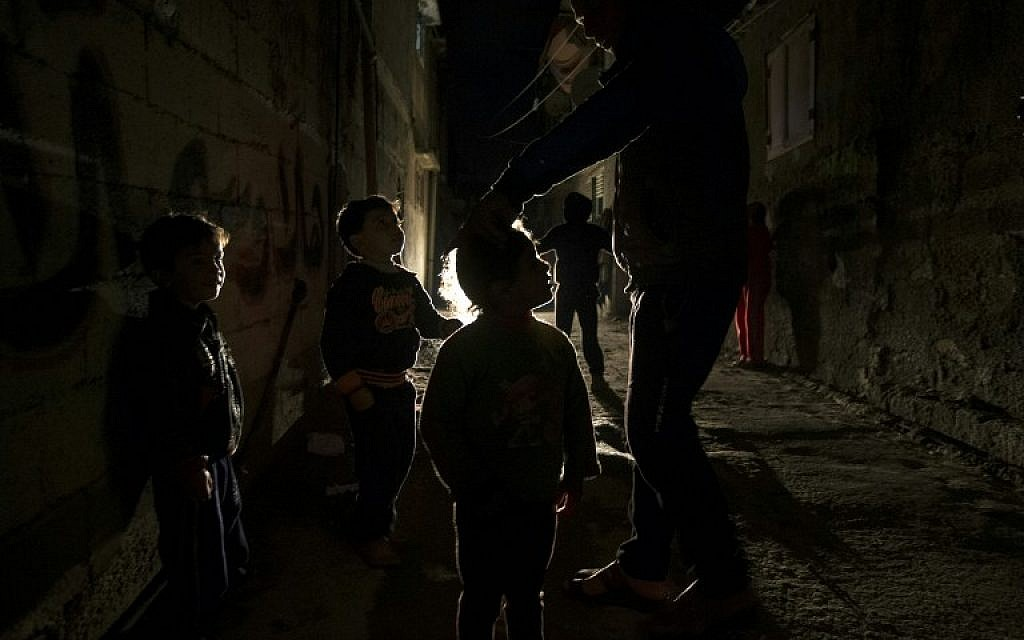 Palestinian children play on a street during a power cut in the Al-Shati refugee camp in Gaza City, on January 4, 2017. (AFP PHOTO / MAHMUD HAMS)