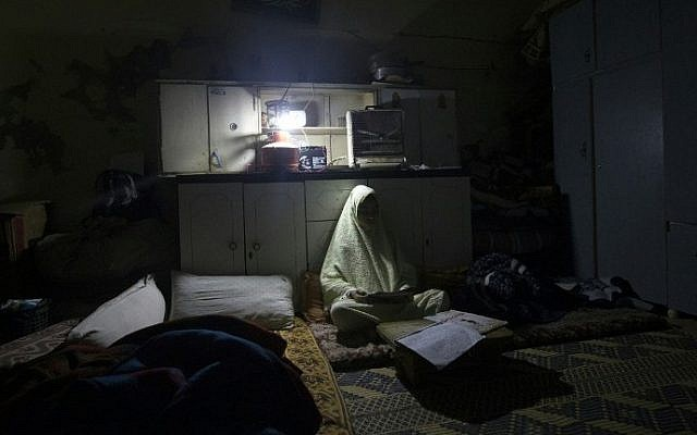 A Palestinian girl does her homework during a power cut in the Al-Shati refugee camp in Gaza City, on January 4, 2017. (AFP/Mahmud Hams)