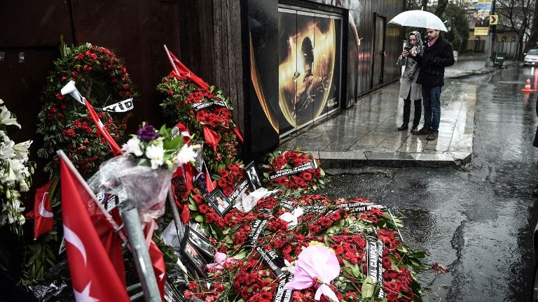 People take pictures of a makeshift memorial set in front of the Reina nightclub on January 5, 2017 in Istanbul, four days after a gunman killed 39 people on New Year's night. (AFP PHOTO / OZAN KOSE)