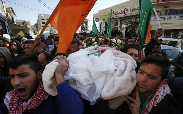 Mourners attend the funeral of Mohammed Rajabi, a Palestinian who was killed after carrying out a stabbing attack against Israeli soldiers months ago, in the West Bank town of Hebron on January 7, 2017, after his body was returned by Israeli authorities. (AFP/Hazem Bader)