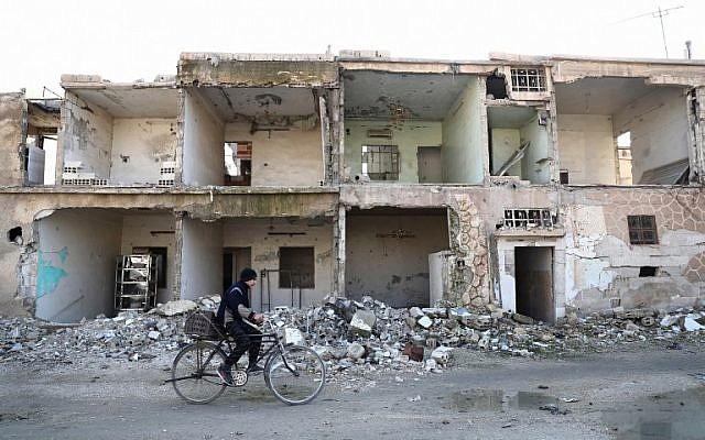 A Syrian man rides a bicycle past destroyed buildings in the rebel-held town of Douma, on the eastern outskirts of the capital Damascus, on January 7, 2017.(AFP Photo/Abd Doumany)