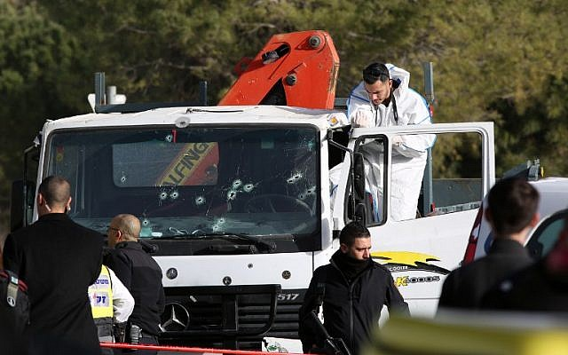 An Israeli forensics expert gathers evidence as security forces and emergency personnel gather at the site of a vehicle-ramming attack in Jerusalem on January 8, 2017. (AFP/ MENAHEM KAHANA)