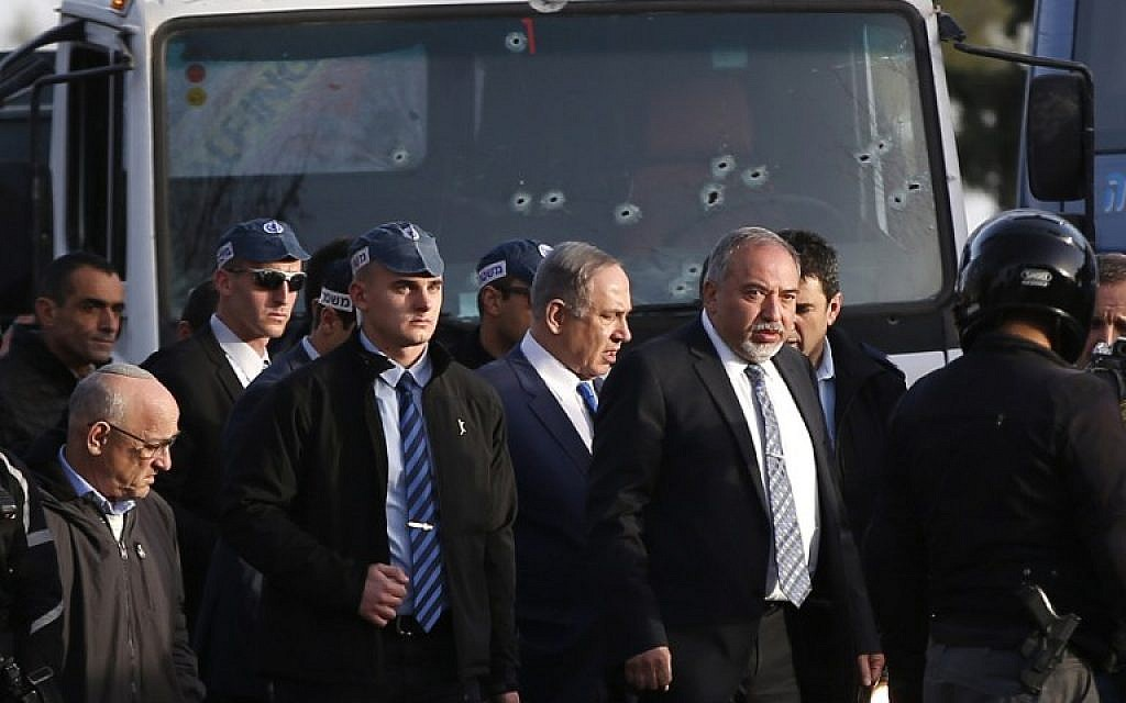 Prime Minister Benjamin Netanyahu, center, and Defense Minister Avigdor Lieberman, to his left, visit the site of a vehicle-ramming attack in Jerusalem on January 8, 2017. (AFP/AHMAD GHARABLI)