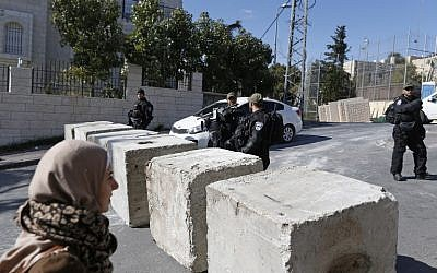 Israeli security forces stand next to newly-installed concrete blocks in the East Jerusalem neighborhood of Jabel Mukaber on December 9, 2017. (AFP/AHMAD GHARABLI)