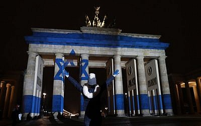 A woman strikes a pose in front of the Brandenburg Gate with the Israeli flag projected onto in Berlin, on January 9, 2017, to pay tribute to the victims of the ramming attack in Jerusalem. (AFP PHOTO / Odd ANDERSEN)