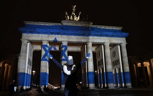 A woman strikes a pose in front of the Brandenburg Gate with the Israeli flag projected onto in Berlin, on January 9, 2017 to pay tribute to the victims of the ramming attack in Jerusalem. (AFP PHOTO / Odd ANDERSEN)