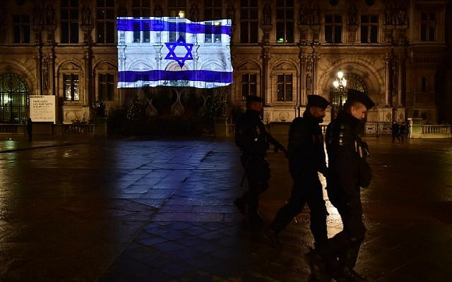 French CRS anti-riot police officers patrol as the Israeli flag is projected onto the facade of the Hotel de Ville in Paris on the night of January 10, 2017, in tribute to the victims of an attack in Jerusalem on January 8.( AFP PHOTO / CHRISTOPHE ARCHAMBAULT)