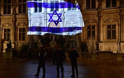 French CRS anti-riot police officers patrol as the Israeli flag is projected onto the facade of the Hotel de Ville in Paris on the night of January 10, 2017, in tribute to the victims of an attack in Jerusalem on January 8.(AFP PHOTO / CHRISTOPHE ARCHAMBAULT)