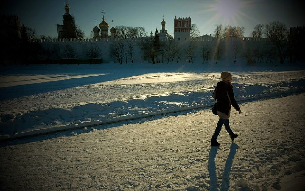 A woman walks along a snow-covered frozen pond near Moscow's Novodevichy Convent on January 11, 2017. (AFP/Yuri KADOBNOV)