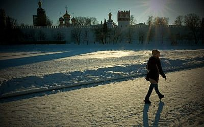 A woman walks along a snow-covered frozen pond near Moscow's Novodevichy Convent in air temperatures of about minus 10 degrees Celsius on January 11, 2017. (AFP Photo/Yuri Kadobnov)