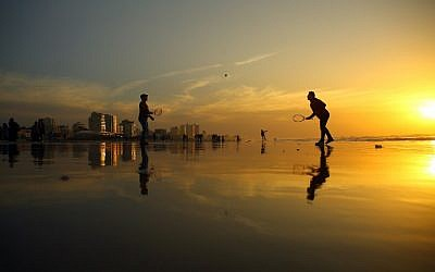 Palestinians play tennis on the beach during the sunset in Gaza City on January 11, 2017. (AFP/MOHAMMED ABED)