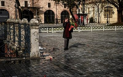 Sibel Satiroglu, a tour guide places red carnations Sultanahmet Square, the site where 12 of her German clients were killed last year in a bombing, in Istanbul on January 12, 2017.(AFP PHOTO / OZAN KOSE)