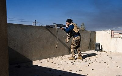 An Iraqi army soldier fires his machine gun at Islamic State positions in Mosul's al-Sahiroun neighborhood on January 12, 2017. (AFP/Dimitar Dolkoff)