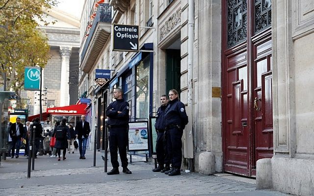 This file photo taken at the Rue Tronchet, near Madeleine, central Paris, on October 3, 2016 shows police officers standing guard at the entrance of the hotel residence, where US reality television star Kim Kardashian was robbed at gunpoint by assailants disguised as police who made off with millions, mainly in jewelry. (AFP PHOTO / Thomas SAMSON)