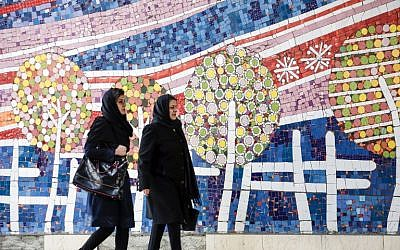 Two Iranian women walk along a street past a mosaic mural on the first anniversary of the nuclear agreement, in the capital Tehran on January 14, 2017. (AFP/ATTA KENARE)