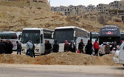 Syrians gather around buses as they prepare to leave the town of Ain al-Fijah, in the Wadi Barada region, on January 14, 2017. (AFP/Stringer)