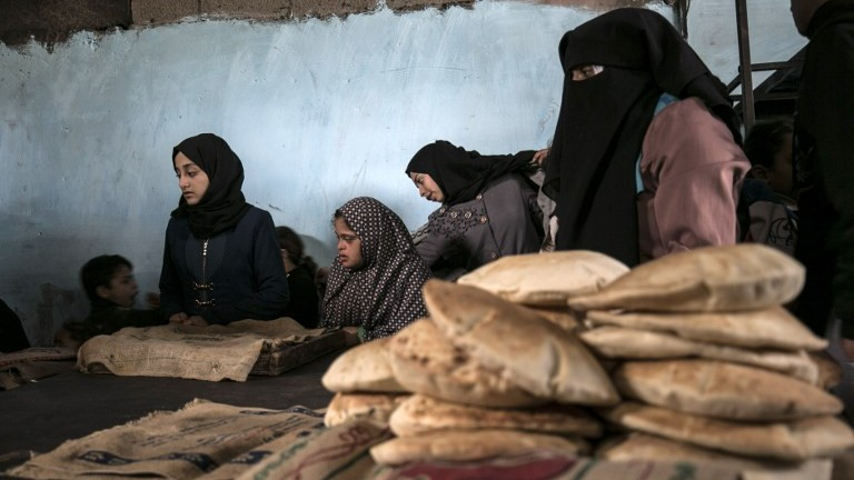 Palestinians collect freshly-baked bread at a traditional wood oven in the Rafah refugee camp, in the southern Gaza Strip on January 14, 2017. (AFP Photo/Said Khatib)
