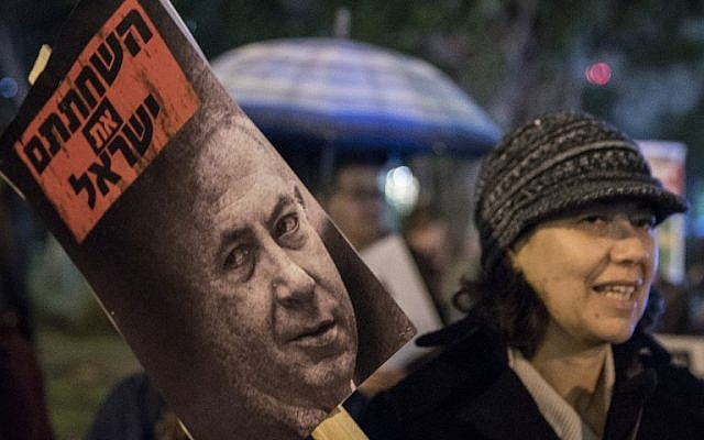 An Israeli left-wing supporter holds a banner reading in Hebrew: ''corrupted the Israelis'' during a rally against Israeli Prime Minister Benjamin Netanyahu and government policies, on January 14, 2017, at the Rabin Square in the city of Tel Aviv (AFP PHOTO / JACK GUEZ)