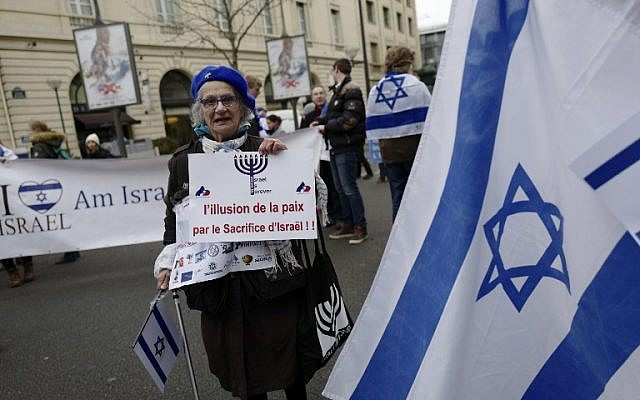"""A woman holds a sign reading """"The illusion of peace by the sacrifice of Israel"""" during a protest rally  against the Paris Middle East peace conference, January 15, 2017. (AFP/Pierre CONSTANT)"""