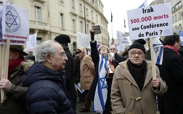 """A man holds a sign reading """"Iraq 500000 dead: a Paris Conference?"""" during a protest rally against the Paris Middle East peace conference, in Paris January 15, 2017 . (AFP/Pierre CONSTANT)"""