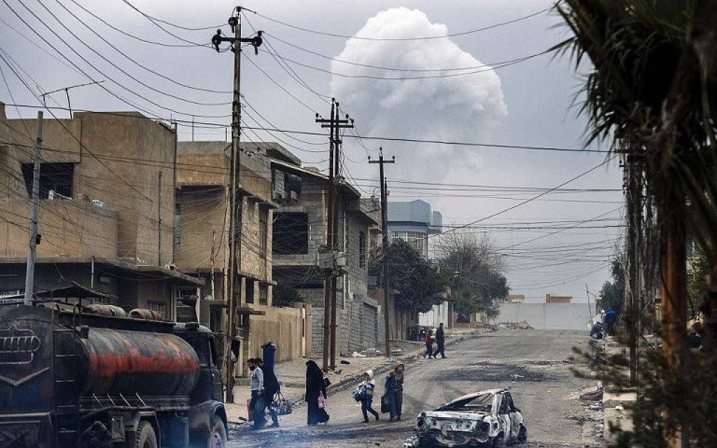 Iraqis walk down a street while smoke rises in the background following a car bomb explosion in eastern Mosul, on January 15, 2017. (AFP / Dimitar DILKOFF)