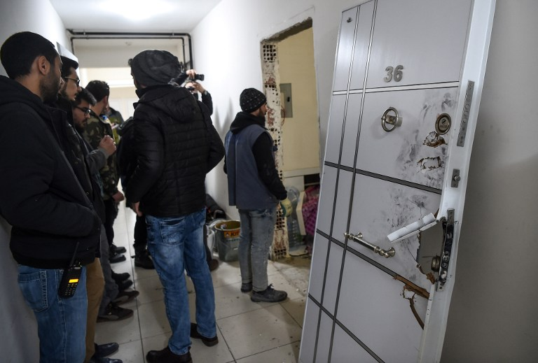Turkish plain clothes police officers wait next to a damaged door at the apartment where Abdulgadir Masharipov, the main suspect in the Reina nightclub terror attack, was arrested by Turkish police the night before, in Istanbul on January 17, 2017. (AFP PHOTO / OZAN KOSE)