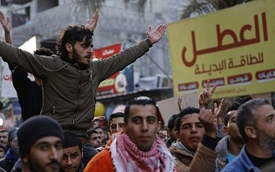 Palestinian activist Mohammed al-Taluli (top), 25, chants slogans during a protest at the Jabaliya refugee camp in the northern Gaza Strip on January 12, 2017, against the Palestinian enclave's ongoing electricity crisis. (AFP Photo/Mohammed Abed)