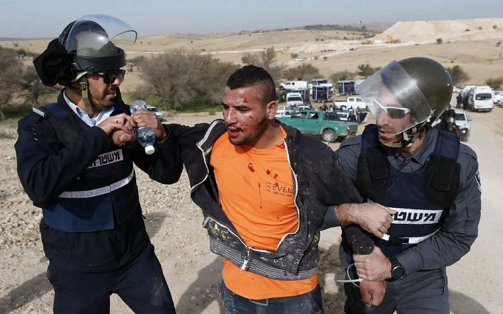 Israeli policemen detain a Bedouin man during a protest against home demolitions on January 18, 2017 in the Bedouin village of Umm al-Hiran, which is not recognized by the Israeli government, near the southern city of Beersheba, in the Negev desert. An Israeli police officer was killed in a car-ramming attack at the scene (AFP PHOTO / AHMAD GHARABLI)