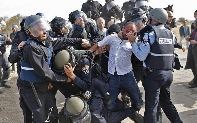 Israeli policemen detain a Bedouin man during a protest against home demolitions on January 18, 2017, in the unrecognized Bedouin village of Umm al-Hiran in the Negev desert. (AFP Photo/Ahmad Gharabli)