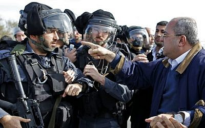 Joint (Arab) List MK Ahmad Tibi, right, confronts an Israeli policeman in a tense standoff with Bedouin protesters in the unrecognized village of Umm al-Hiran in the Negev desert, on January 18, 2017. (AFP Photo/Ahmad Gharabli)