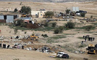 Israeli policemen stand guard as bulldozers demolish homes in the unrecognized Bedouin village of Umm al-Hiran in the Negev desert, on January 18, 2017. (AFP Photo/Menahem Kahana)