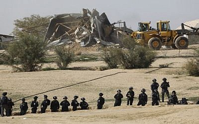 Israeli policemen stand guard as bulldozers demolish homes in the unrecognized Bedouin village of Umm al-Hiran in the Negev desert, on January 18, 2017. (AFP/Menahem Kahana)