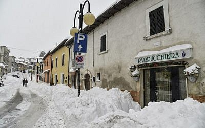 People walk in the snow in Monterale's main street, near Amatrice, after a 5.7-magnitude earthquake struck the region, on January 18, 2017. (AFP/ANDREAS SOLARO)